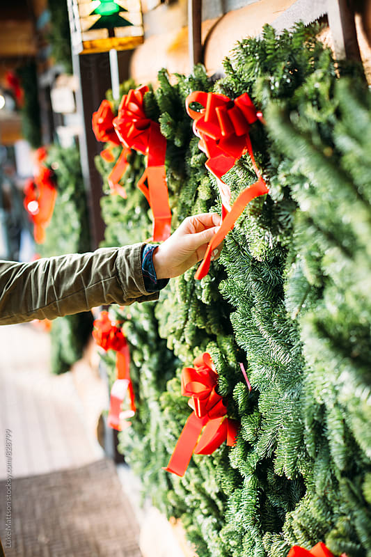 Hand Of Young Woman Reaching Out To Touch Christmas Wreaths Hanging On Wall by Luke Mattson for Stocksy United