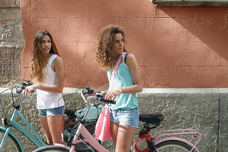 Two young girls standing with bikes in a city  by Miquel Llonch for Stocksy United