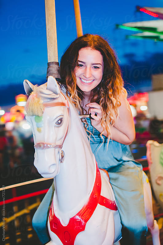 A young woman on a carousel at the carnival by Chelsea Victoria for Stocksy United