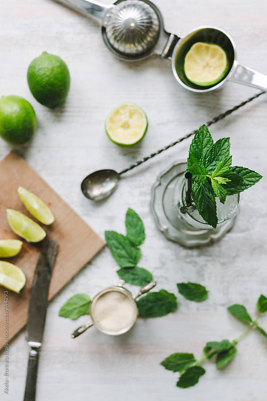 mojito ingredients from above on a white wooden board by Leander Nardin for Stocksy United