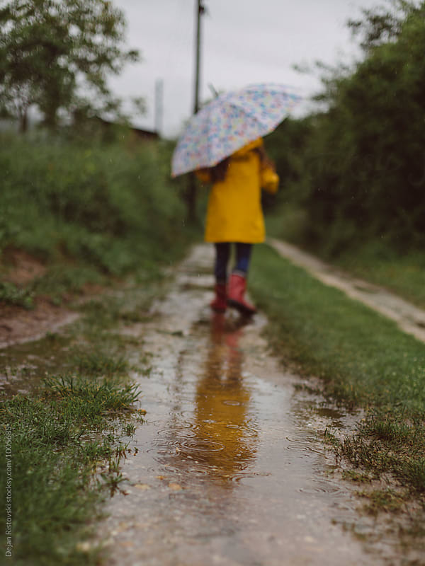 Girl walking under umbrella. by Dejan Ristovski for Stocksy United