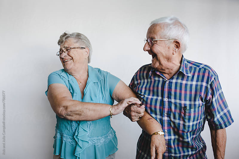 Funny old man pranking his wife by removing dentures during photo shoot by Rob and Julia Campbell for Stocksy United