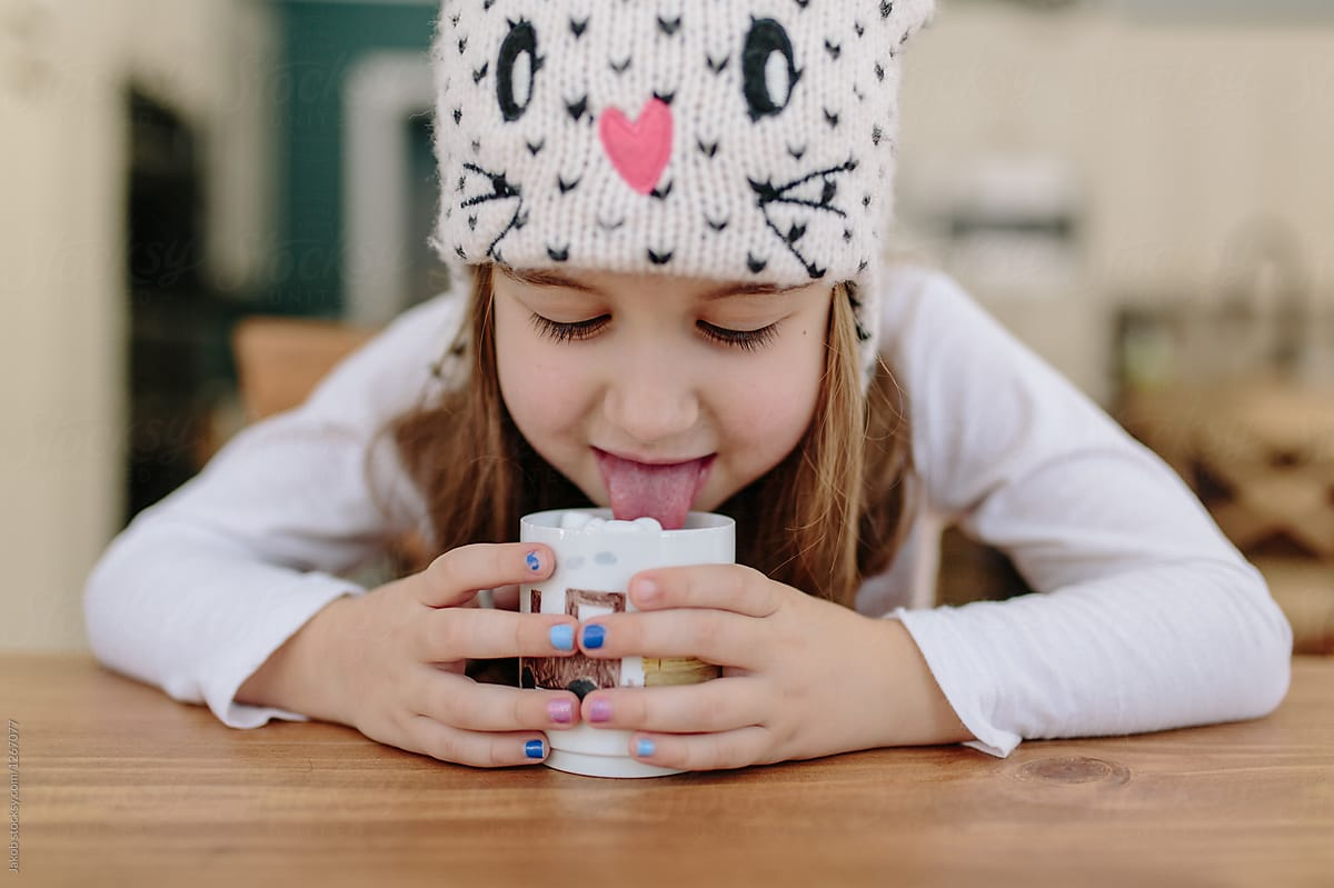 7033c8034684 Cute Young Girl In A Winter Hat Drinking Hot Chocolate With ...