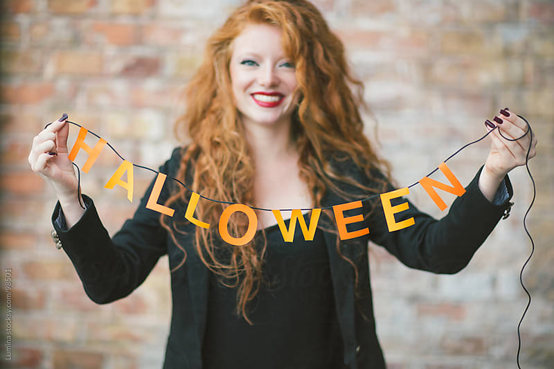 Smiling Ginger Woman Holding Halloween Decoration  by Lumina for Stocksy United