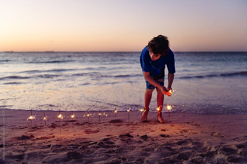 Boy with a line of sparklers in the sand at the beach after sunset by Angela Lumsden for Stocksy United