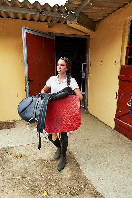 Beautiful brunette jockey carrying horseback saddle by Guille Faingold for Stocksy United