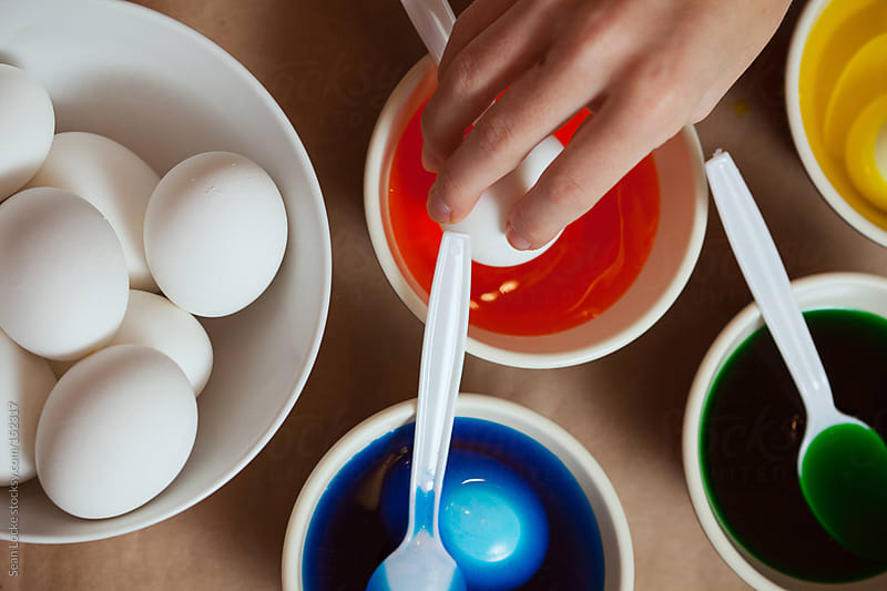 Easter: Putting An Egg Into Orange Dye by Sean Locke for Stocksy United