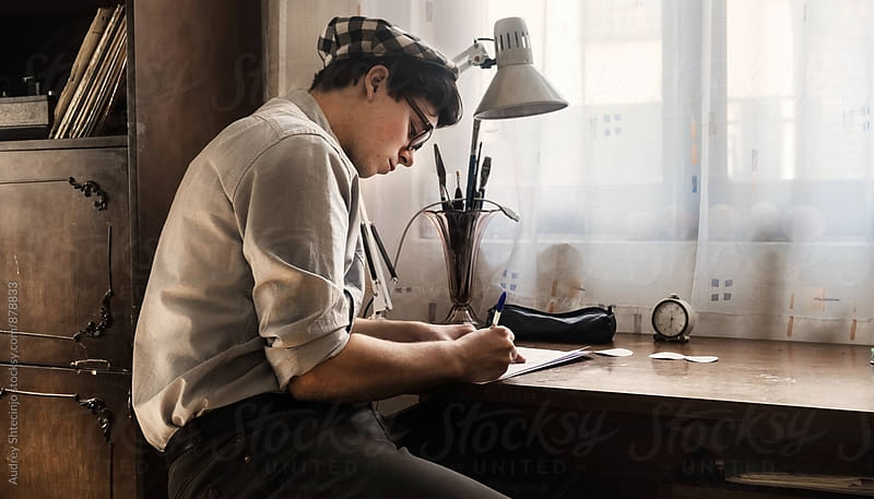 Young stylish man drawing new tattoo sketch on paper in vintage studio. by Marko Milanovic for Stocksy United
