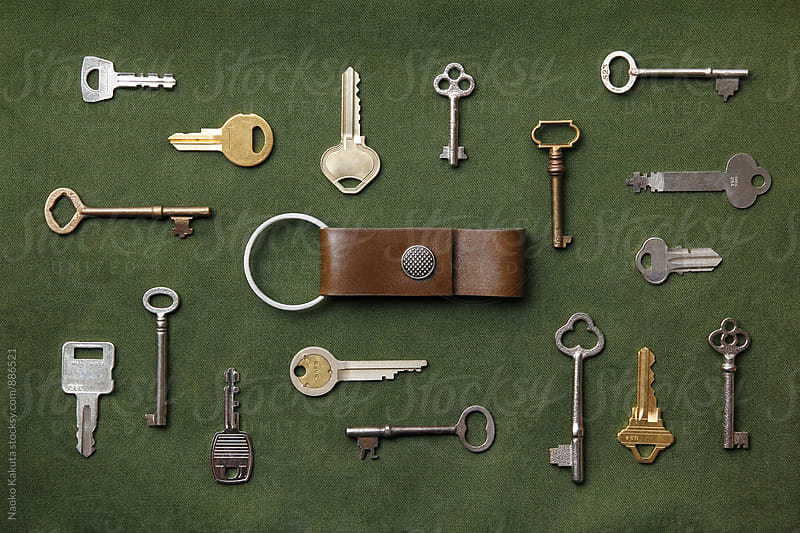 keys arranged around a key chain on green canvas fabric by Naoko Kakuta for Stocksy United