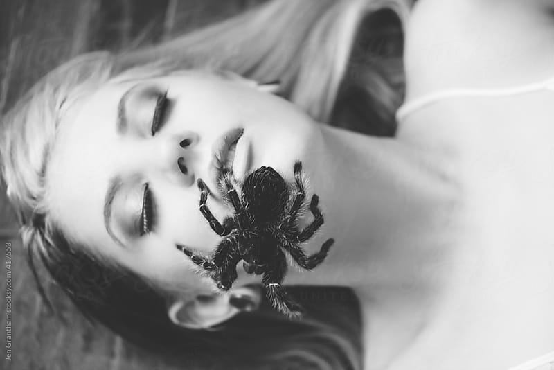 Tarantula crawling on woman's face by Jen Grantham for Stocksy United