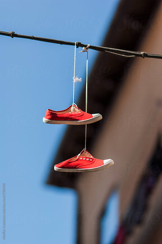 Sport shoes hanging from phone wire by Marilar Irastorza for Stocksy United
