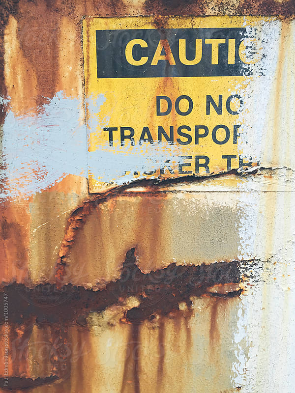 Caution sign on rusty metal wall, close up by Paul Edmondson for Stocksy United