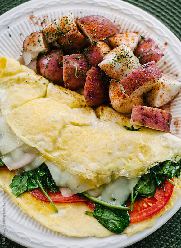 Omelet breakfast and potatoes  by Matthew Spaulding for Stocksy United