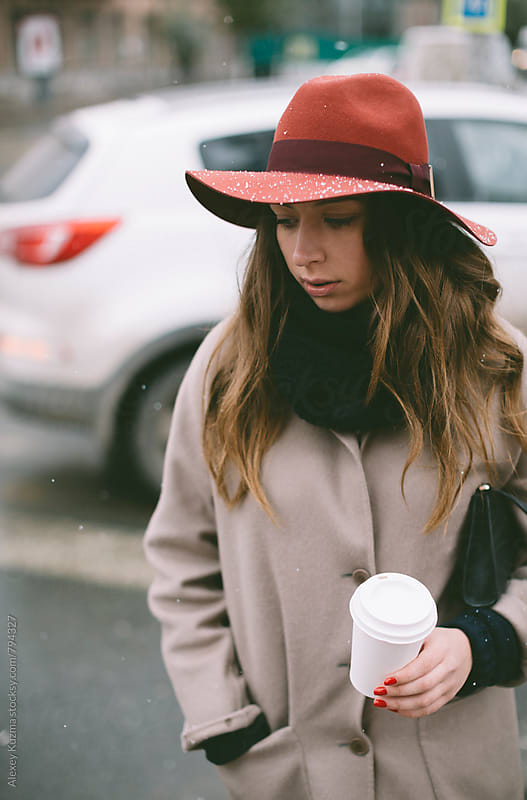 winter portrait of young woman with red hat on the street by Alexey Kuzma for Stocksy United
