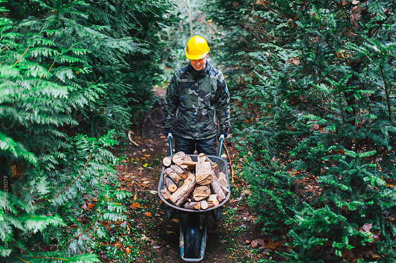 A lumberjack with a wheelbarrow full of wood by Ivo de Bruijn for Stocksy United