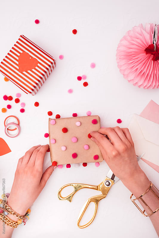 Woman Decorating Valentine's Day Gift With Pompons  by Katarina Radovic for Stocksy United