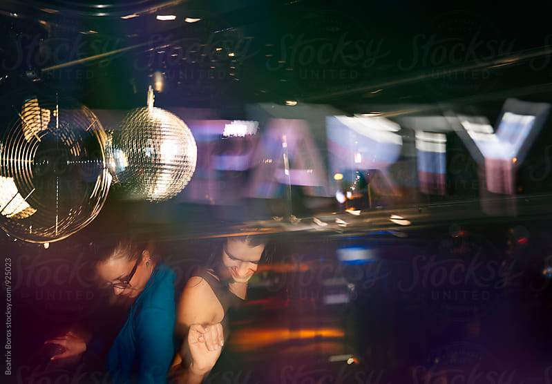 Two women dancing together in a club by night by Beatrix Boros for Stocksy United