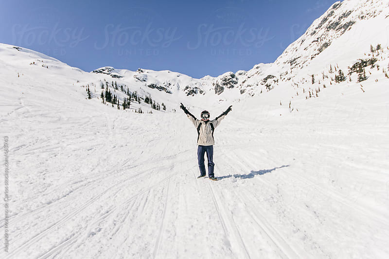 Young victorious man rising his arms on a snow covered valley on mountain landscape by Alejandro Moreno de Carlos for Stocksy United
