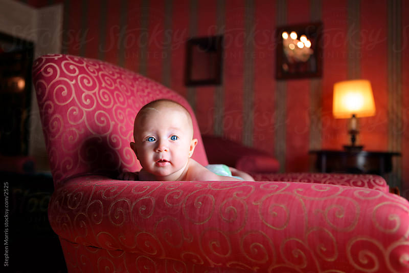 Baby Girl in Oversized Arm Chair by Stephen Morris for Stocksy United