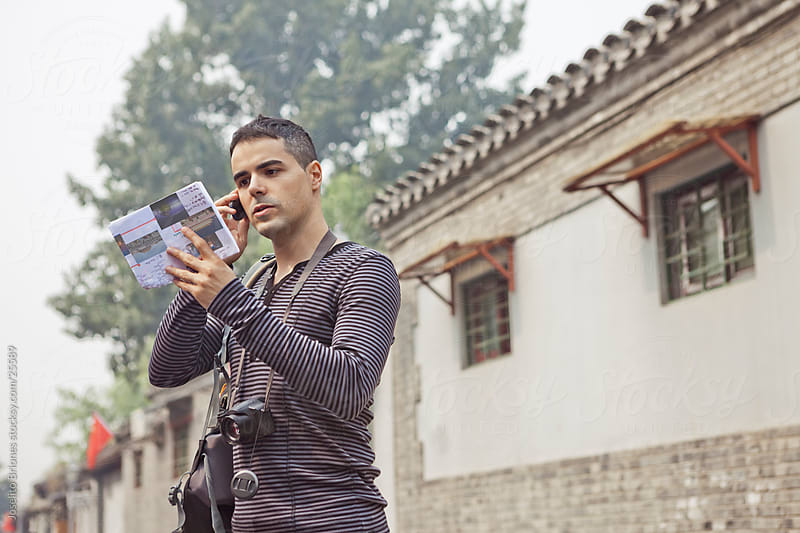 Young Male European Tourist in China Talking on his Cell Phone by Joselito Briones for Stocksy United