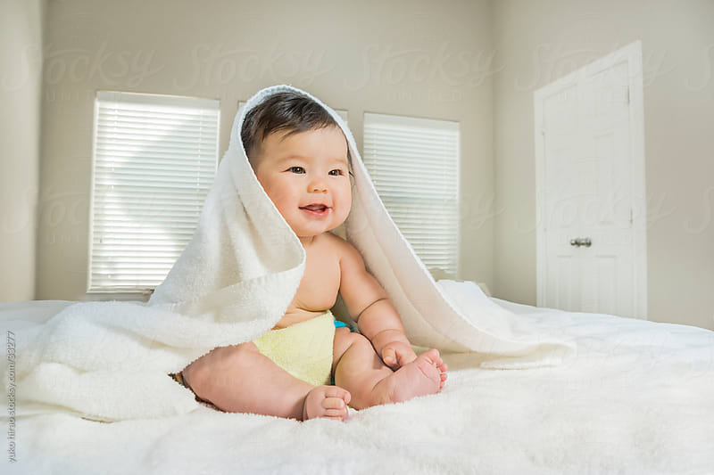 Baby girl with a towel in bedroom by yuko hirao for Stocksy United