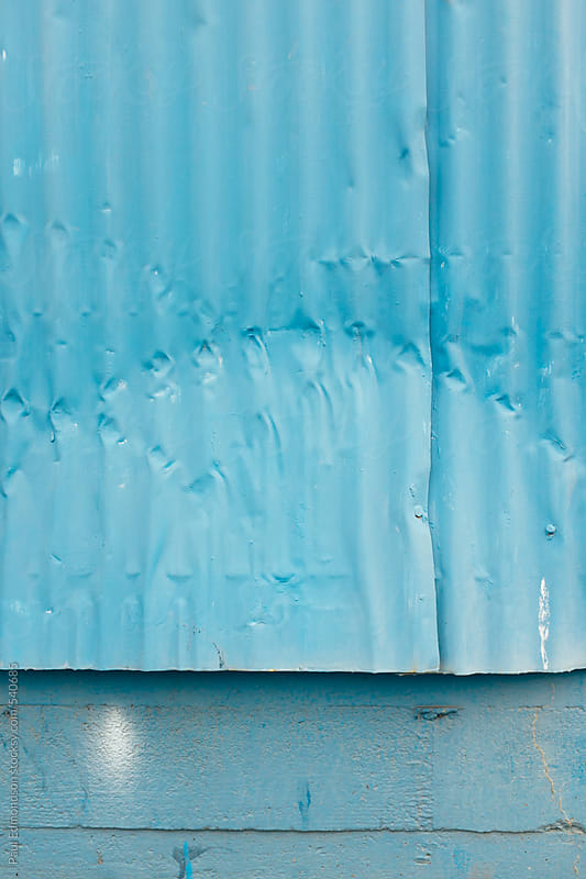 Painted blue metal siding of warehouse exterior, close up by Paul Edmondson for Stocksy United