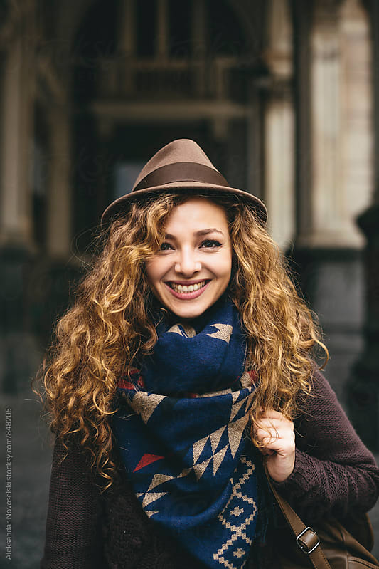 Cute young woman smiling at camera in urban environment by Aleksandar Novoselski for Stocksy United