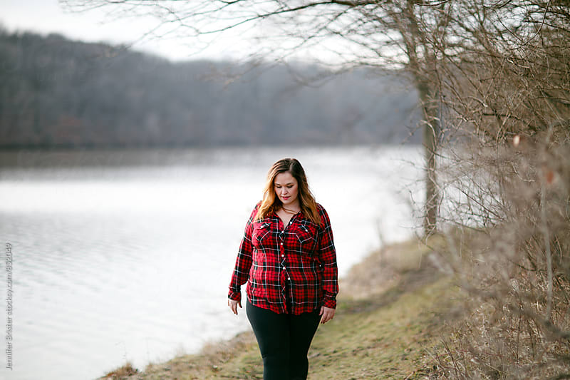 A beautiful woman walks along lake by Jennifer Brister for Stocksy United