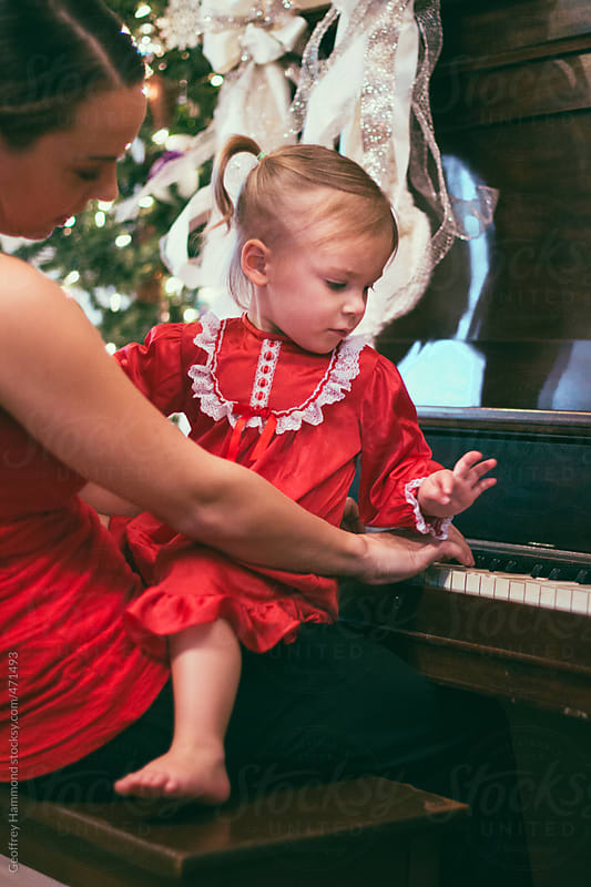 Mother and Daughter Sitting and Playing Piano at Christmas by Geoffrey Hammond for Stocksy United