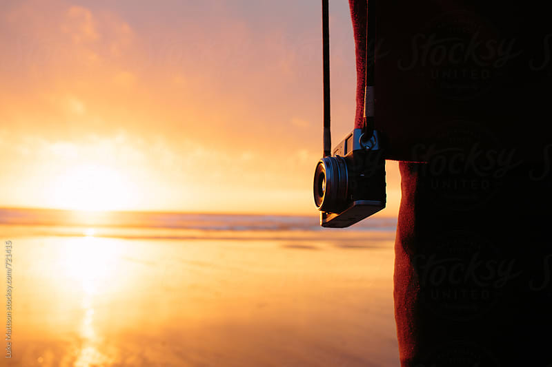A Camera Hangs At The Side Of A Person Watching The Sun Set Over The Pacific Ocean From The Shore by Luke Mattson for Stocksy United