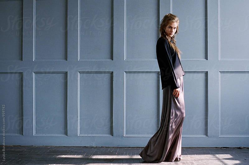 Young woman walking along light-blue wall by Lyuba Burakova for Stocksy United