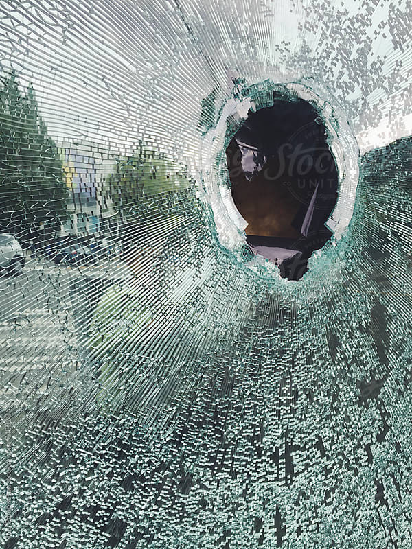 Hole in broken shattered glass window  by Paul Edmondson for Stocksy United
