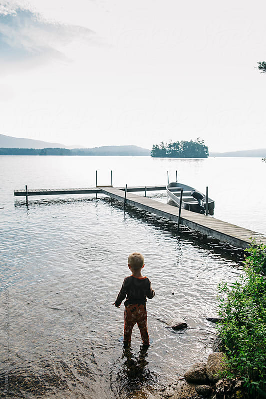 Child Playing at Lake Early Morning by Raymond Forbes LLC for Stocksy United
