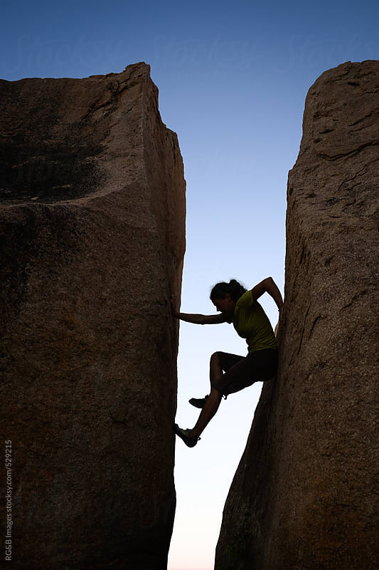Woman silhouette climbing between two rock walls by RG&B Images for Stocksy United