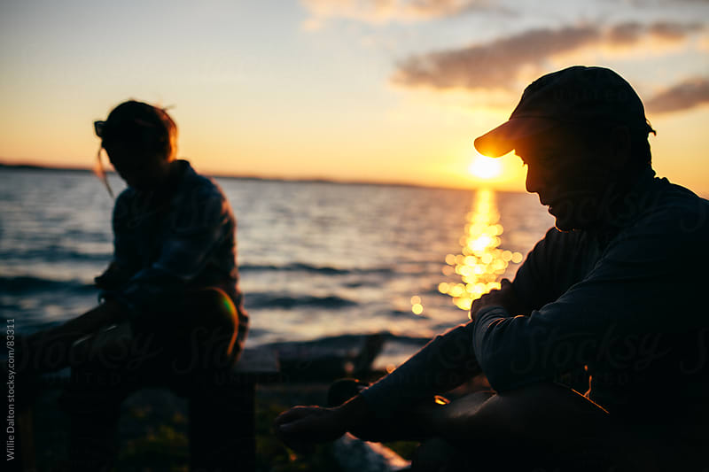 Man and Woman Silhouetted during a Lakeside Sunset by Willie Dalton for Stocksy United