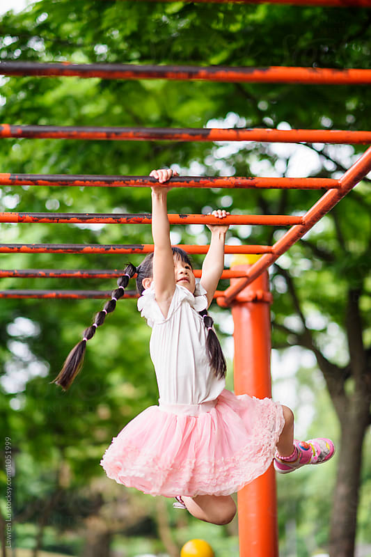 Portrait of little cute girl hanging on metal bars at playground by Lawren Lu for Stocksy United