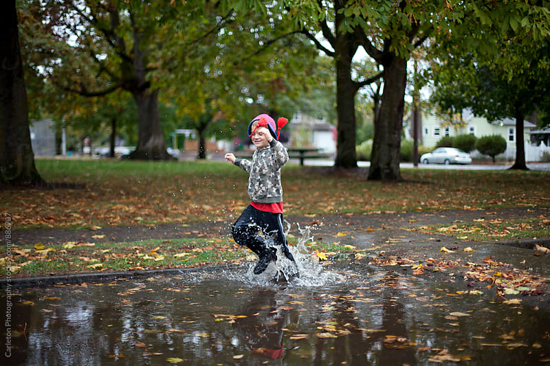 Boy finds happiness in a huge rain puddle in Portland, Oregon by Carleton Photography for Stocksy United