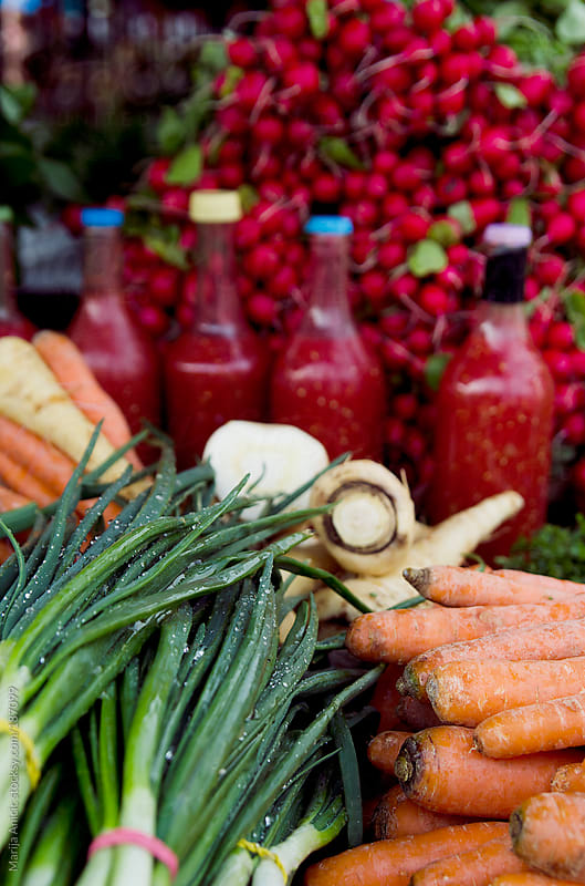 Bottles of fresh organic tomato juice with green onions,carrots,beets and parsnip on the market by Marija Anicic for Stocksy United