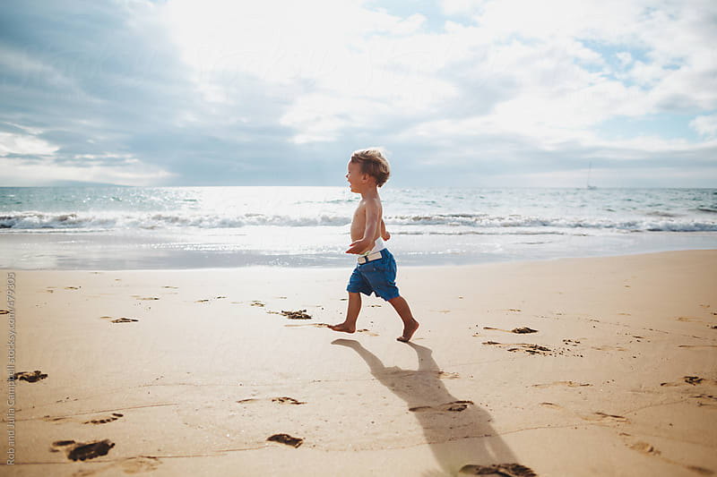 Toddler boy running on sandy tropical beach alone by Rob and Julia Campbell for Stocksy United
