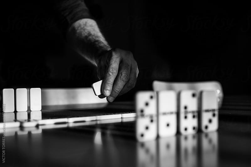 Man Playing Domino by VICTOR TORRES for Stocksy United