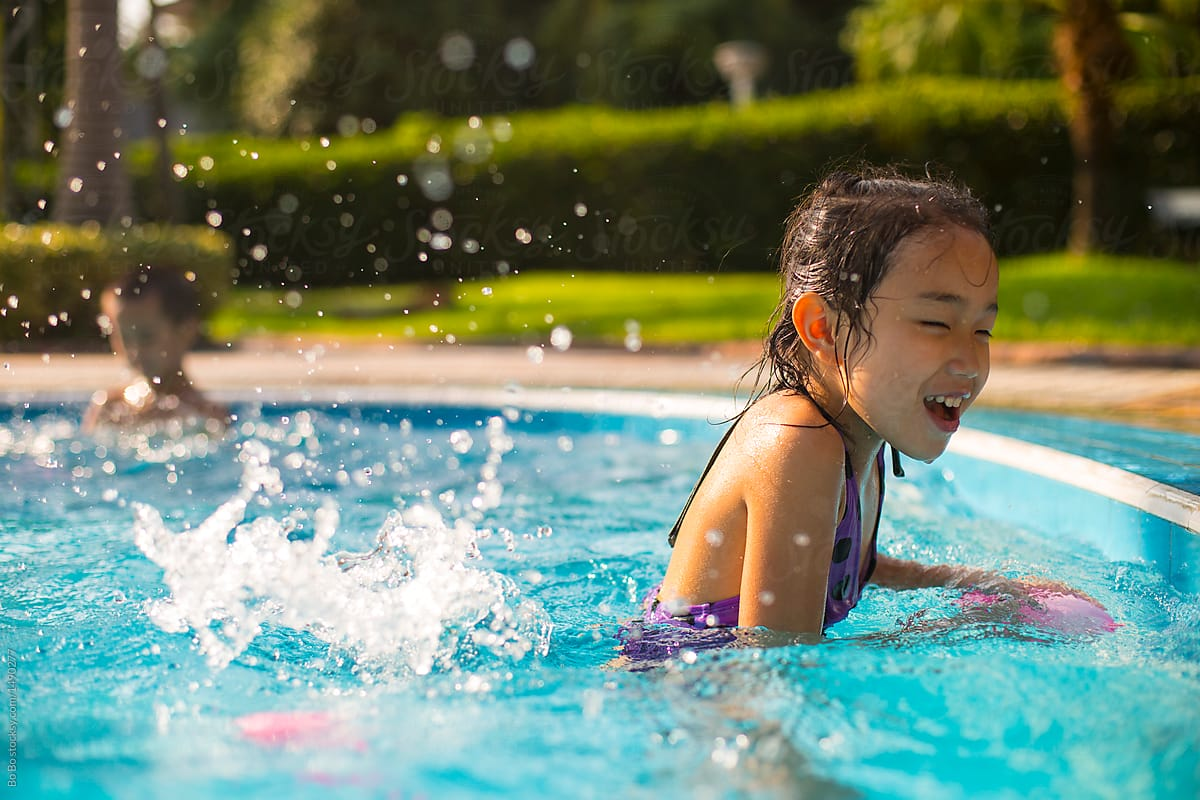 Two Happy Asian Kids Playing In The Swimming Pool   Stocksy United