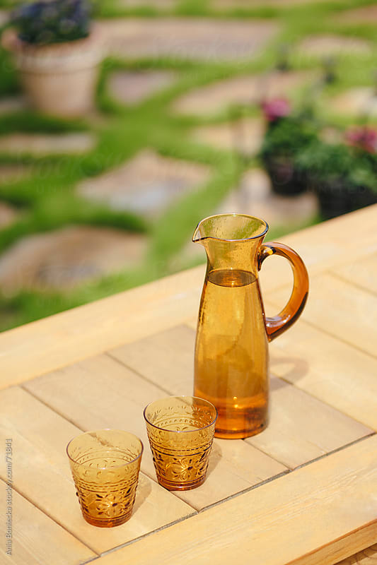 A pitcher of water and two glasses outside in the summer by Ania Boniecka for Stocksy United