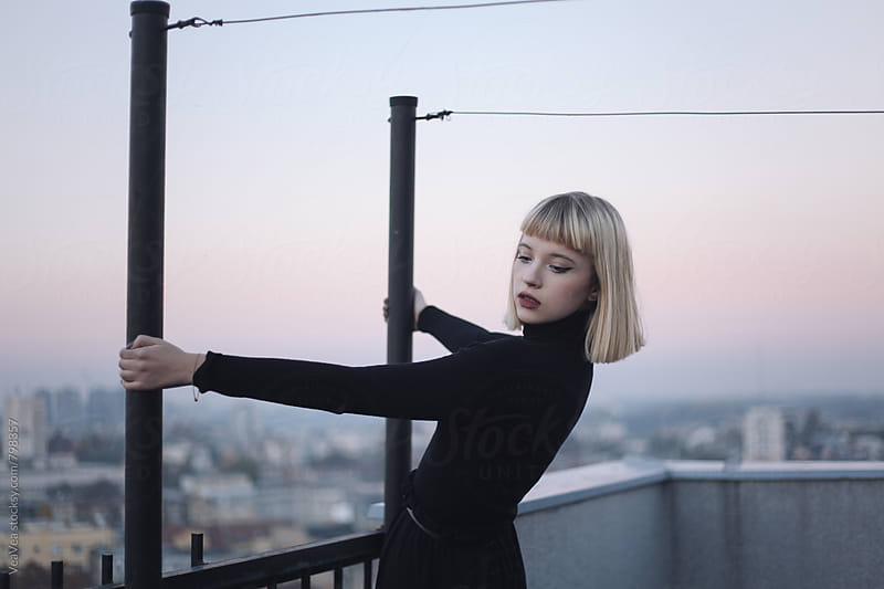 Beautiful blonde woman on the roof of the building during sunset by Marija Mandic for Stocksy United