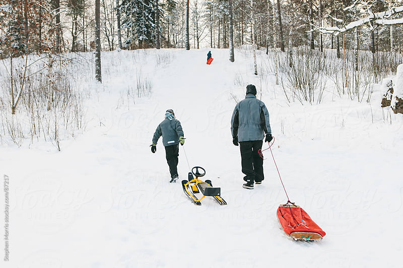 Father and Son Pulling Sleds Uphill by Stephen Morris for Stocksy United