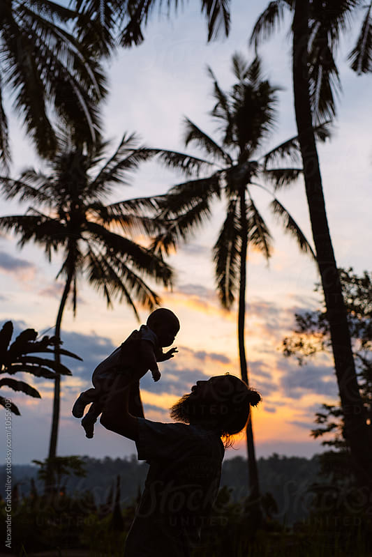 Father Holding Son Up Into the Air At Tropical Sunset by Alexander Grabchilev for Stocksy United