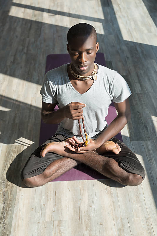 Fit young man meditating in a lotus yoga position in a fitness studio  by Jovo Jovanovic for Stocksy United