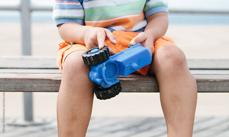 Young boy sitting on a wooden bench pointing to his plastic toy car by Mihael Blikshteyn for Stocksy United