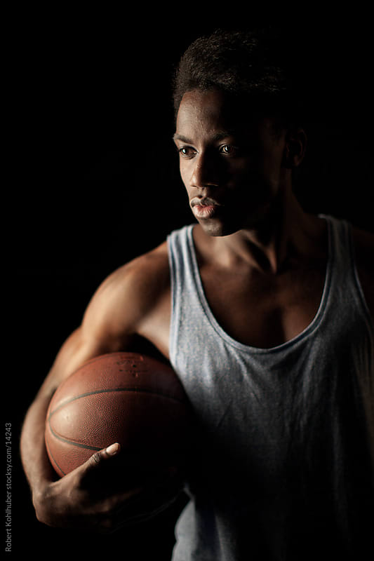 Young black man with basketball by Robert Kohlhuber for Stocksy United