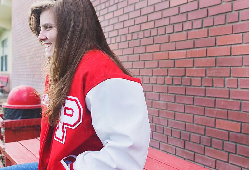 Teenage girl wearing letterman jacket sits on table by Tana Teel for Stocksy United