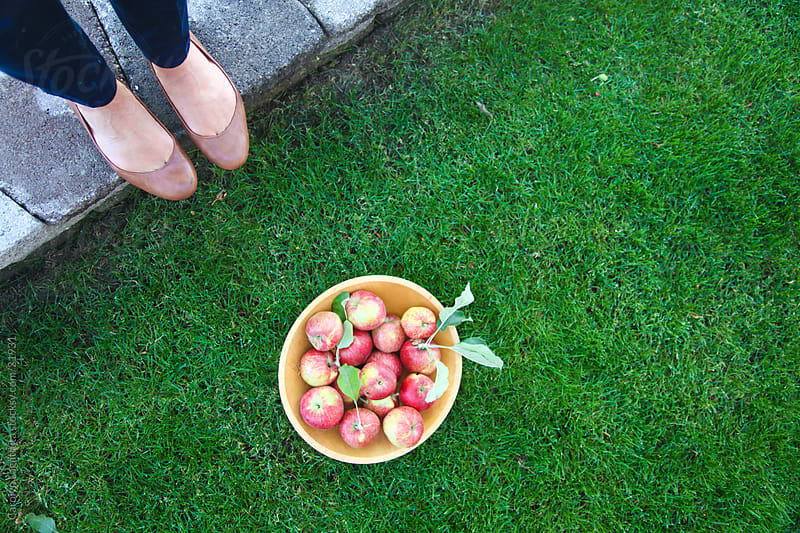 Apples in wooden bowl on some grass with a pair of feet next to it. by Carolyn Lagattuta for Stocksy United